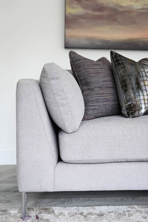 Simply-Home-Decorating_Lori-Steeves_Vancouver-BC_Canadian-Designer_How-to-Avoid-5-Huge-Home-Furnishing-Mistakes_Contemporary-Light-Gray-Sofa-in-Living-Room-with-Artwork-and-Pillows